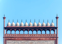 Line of chhatris, small white domes on top of gate at Agra's Taj Mahal complex in India.