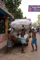 Three men needed to put one bale on the back of one man.