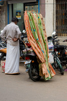 Motorized street vendor has textiles to sell hung from a pole mounted on his bike.