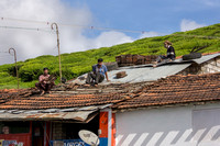 Inspecting and repairing the roof of a humble dwelling.