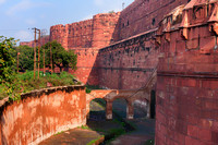 Red ramparts and empty moat of Agra Fort in India.
