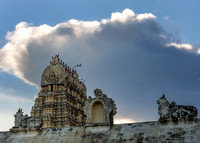 Gopuram peeks over the temple wall with Nandi statues.
