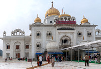 Sikh temple in white marble with golden domes.
