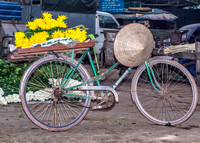Bike with a few flowers at the market.