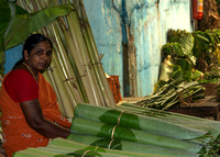 Selling rolled-up banana leaves.
