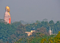 Giant Hindu God statue over the trees and against the city smog.