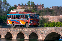 Public transport bus on bridge with Palace in background.