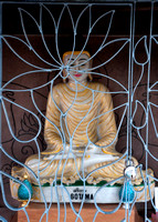 The caged Buddha seen through the fence.